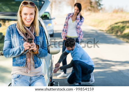 Puncture wheel man changing tire help two female friends