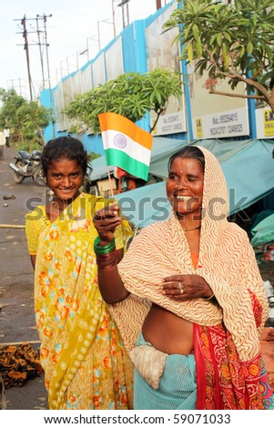 PUNE, MAHARASHTRA/INDIA August 15: A poor street side lady holding the Indian flag on the 64th Indian independence day on August 15, 2010 in Pune, Maharashtra, India.