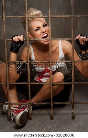Punk girl behind bars. - stock photo