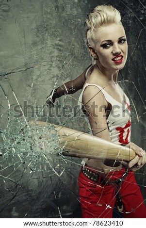 Punk girl broking a glass with a bat