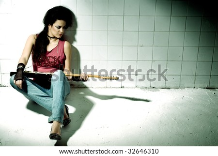 "Punk Girl playing guitar on an ""underground&q uot; background high contrast - stock photo"