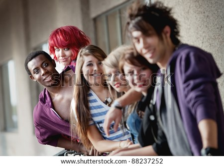 Punk rock looking teens smile at the camera as the camera focuses on the back two individuals.