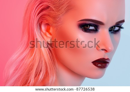 Punk rock style or halloween make-up. Fashion woman model face with bright glamour makeup. Perfect skin, black gloss eyeshadows on eyes and dark brown glossy lips visage. Portrait in red light