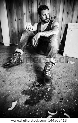Punk rocker or redneck sits on the floor and smoke in a messy house.