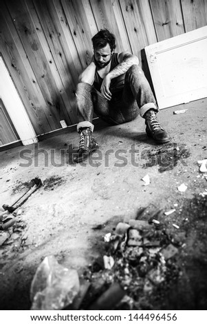 Punk rocker or redneck sits on the floor and think in messy house.