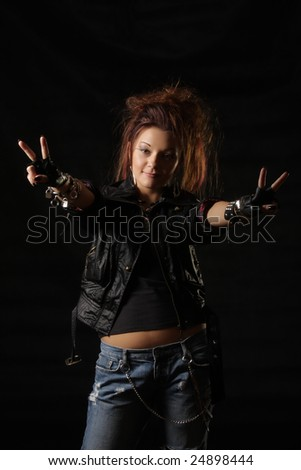 Punky style girl showing two victory signs photo over dark background