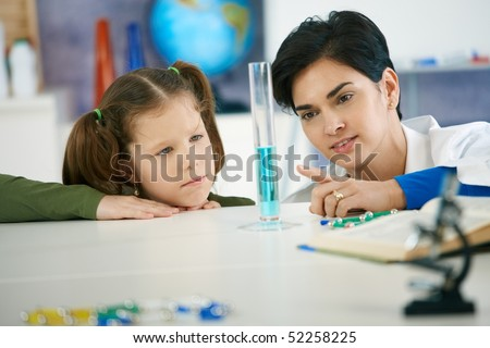 Pupil and teacher looking at test tube in chemisty class at elementary school. Teacher explaining.