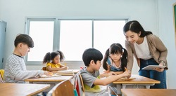 Pupil boy hi five with teacher in classroom at elementary school. Student boy studying in primary school. Children writing notes in classroom. Education knowledge, successful teamwork concept banner