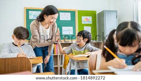 Pupil boy hi five with teacher in classroom at elementary school. Student boy studying in primary school. Children writing notes in classroom. Education knowledge, successful teamwork concept