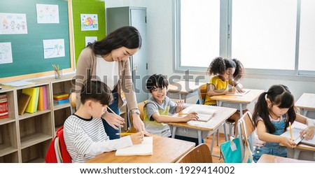 Pupil boy hi five with teacher in classroom at elementary school. Student boy studying in primary school. Children writing notes in classroom. Education knowledge, successful teamwork concept banner Photo stock ©