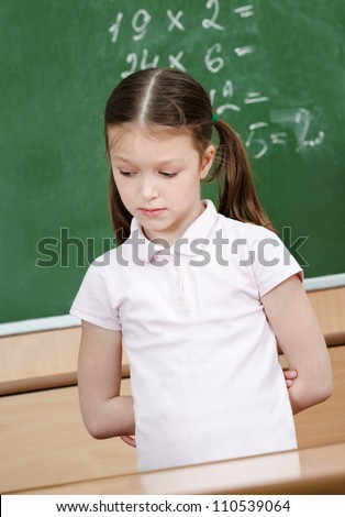 Pupil doesn't know the answer and she is ashamed of it. She puts her hands behind the back