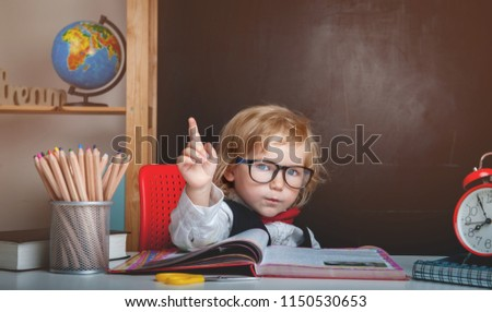 Pupil from primary school in a glasses with raising hand. Child is ready to answer with a blackboard on a background. Back to school. Pencils, alarm clock, globe and books in the class room interior - Shutterstock ID 1150530653