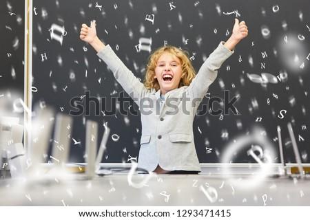 Pupil in elementary school cheers in front of blackboard #1293471415