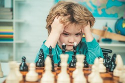 Pupil kid thinking about his next move in a game of chess. Clever concentrated and thinking child while playing chess. Little clever boy thinking about chess. Games good for brain intelligence concept