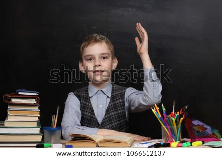 Pupil of junior classes wants to answer at the lessons aganist the backdrop of a black board #1066512137