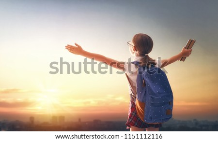 Pupil of primary school with book in hand. Girl with backpack on sunset background. Beginning of lessons. First day of fall.