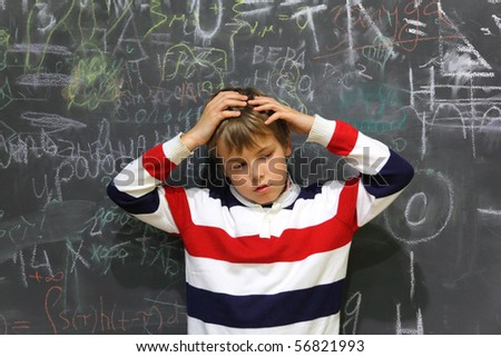 pupil standing near school board and hold on his head half body sad face