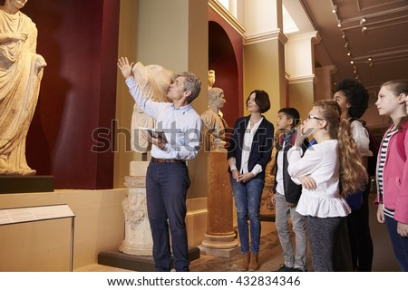 Pupils And Teacher On School Field Trip To Museum With Guide ストックフォト ©