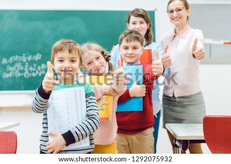 Pupils and teacher showing thumbs-up in school having fun in class