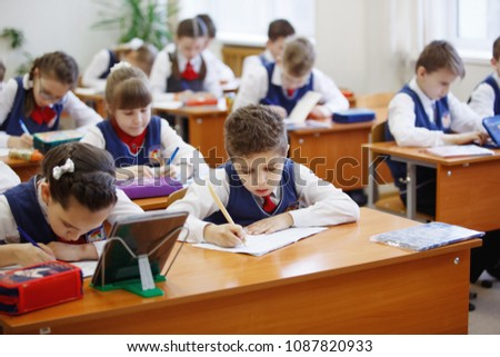 Pupils at the desk think and decide the task in the school. Primary education, training and people concept #1087820933