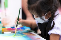 Pupils girl are concentrating on drawing and painting with brush and watercolor on the canvas. An Asian little child is wearing a white cloth face mask while learning to paint. Child 3 years old.