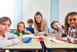 Pupils in a class of a primary school in the tutoring class with teacher