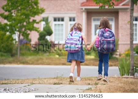 Pupils of primary school. Girls with backpacks near building outdoors. Beginning of lessons. First day of fall. #1145296625