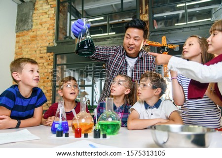 Pupils of primary school watch carefully for their teacher who shows interesting chemical experiments with colored liquids in glass flaks.