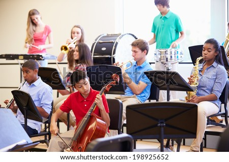 Pupils Playing Musical Instruments In School Orchestra - stock photo