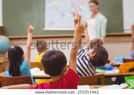 Pupils raising hand during geography lesson in classroom at the elementary school