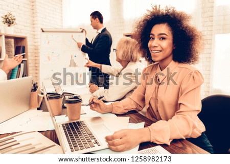 Pupils Studying a Business and Finance. Teacher is Showing New Information to Students. Students is Multiracial People of Different Ages. Black Female Pupil Looking into a Camera. People in Classroom. #1258982173