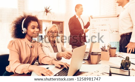 Pupils Studying a English Language. Male Pupil Answering on Teacher Questions at Board. Other Students Students is Using a Laptops. Students is Multiracial People of Different Ages. Classroom. #1258981747