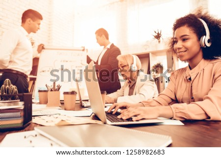 Pupils Studying a English Language. Male Pupil Answering on Teacher Questions at Board. Other Students Students is Using a Laptops. Students is Multiracial People of Different Ages. Classroom. #1258982683