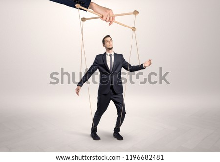 Puppet businessman in an empty room leaded by a huge hand Stockfoto ©