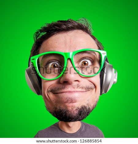 puppet man listening to music with big head on green background