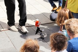 Puppet show watched by children on street. European children play with parents. Acting show in Edinburgh Festival. Open air theatre for kids.  Childhood, playful, happiness and enjoyment image.