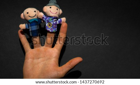 Puppet theater. Hand wearing old people members puppets: elderly granny and grandpa. happy retirement.
