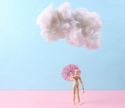 Puppet with umbrella and cloud on a blue-pink background. Rainy concept, weather, minimalism