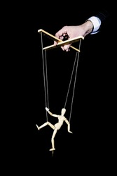 Puppeteer. The hand controls the puppet strings on a black background. Dancing wooden puppet. Manipulation of the people.