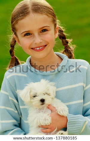 Puppy, child - lovely girl playing with cute puppy in the garden, best friends