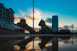 Puppy, sculpture by Jeff Koons.Reflection in the puddle of a part of the city of Bilbao and a sculpture of flowers in the shape of a dog.
