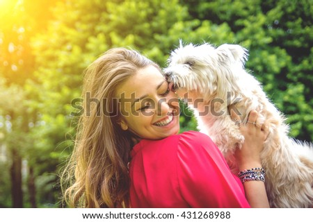 Puppy white dog licking it\'s owner. Attractive caucasian girl having fun with her dog