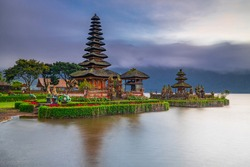 Pura Ulun Danu Bratan temple in Bali island. Beautiful balinese temple during sunrise. Balinese landmark. Cloudy sky. Water reflection. Slow shutter speed. Bratan lake, Bali, Indonesia
