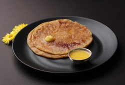 Puran Poli, also known as Holige, is an Indian sweet flatbread from India consumed mostly during Holi festival. Served in a plate with pure Ghee.
