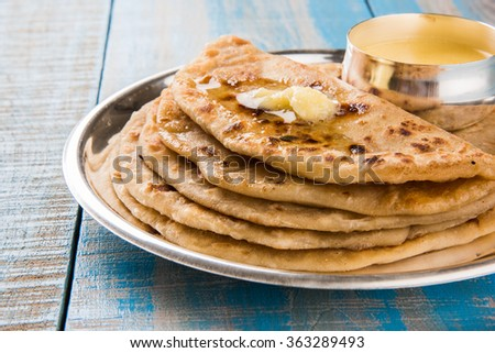 Puran Poli, also known as Holige, is an Indian sweet flatbread from India consumed mostly during Holi festival. Served in a plate with pure Ghee over colourful or wooden background. Selective focus