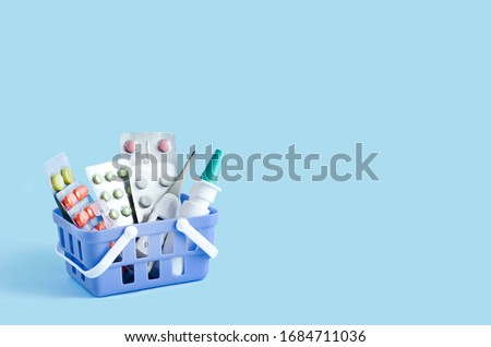 purchase, delivery of medicines to your home. home first aid kit for colds, illnesses, viruses, epidemics. online purchase of medicines. drugs in basket on blue background, copy space