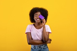 Purchase, money and payment concept. Joyful african american woman covering eye with credit card, wearing casual clothes posing isolated on yellow wall background, studio shot.