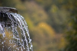 Pure fresh water waterfall in forest in the mountains. Old fontain close up. Selective focus