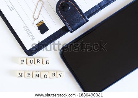 Photo of  Pure memory lettering next to an open blank notebook, micro-sd memory card, smartphone and ejector for ejecting a SIM card. Digital technologies and human memory. Close-up