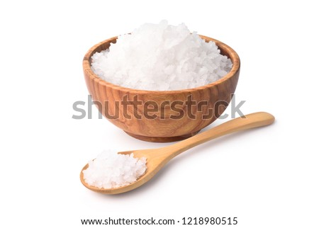 Pure natural sea salt in wooden bowl and wooden spoon isolated on white background.